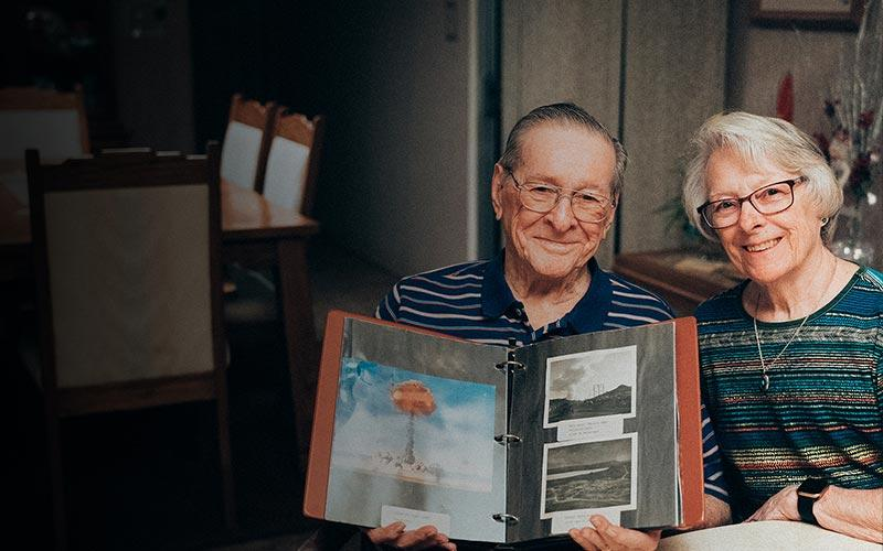 elderly couple with binder of pictures